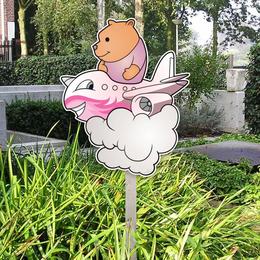 Roze geboortebord van beertje in vliegtuig voor in de tuin